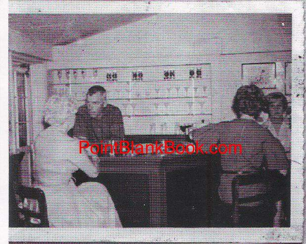 Some time in the late 50s, Lee Marvin holds court behind his home bar while wife Betty holds her gaze on her husband's intake.