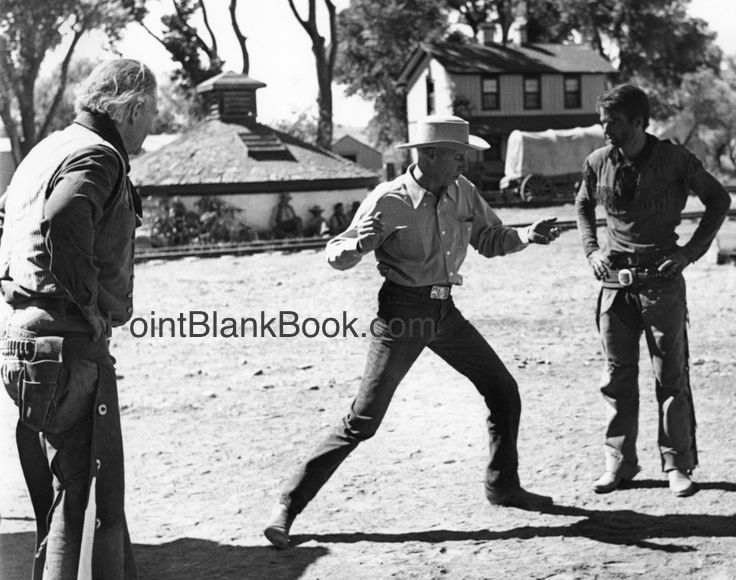 Director Howard Hawks (center) works out the details of REd RIVER'S climatic fight with John Wayne (left) and Montgomery Clift (right).