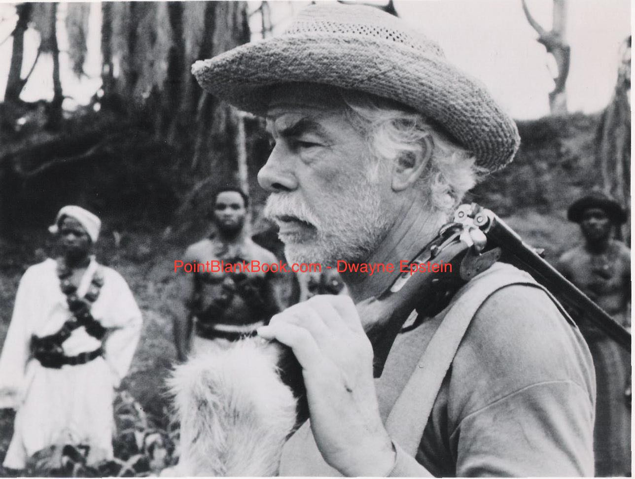 Lee Marvin with loaded elephant gun at the read, set to do battle with man or beast.